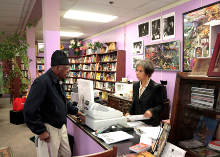 Co-owner Karen Johnson talks with a customer at the counter of Marcus Books.
