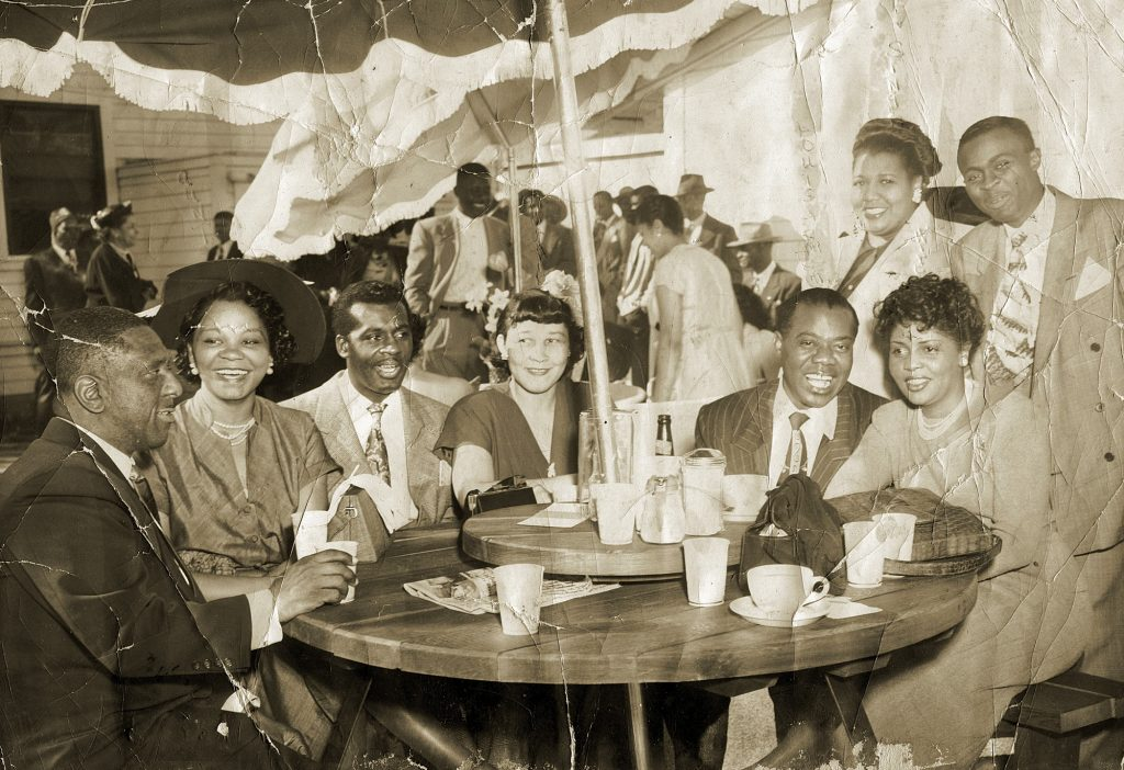 At a party in the Fillmore in the 1940s, jazz great Louis Armstrong (seated second from right with his wife, Lucille) was joined by locals including Gertrude Hall (center), Charles Sullivans's sister and the mother of Blues for Charles playwright Harry Hall. Photo courtesy of the Hall family.