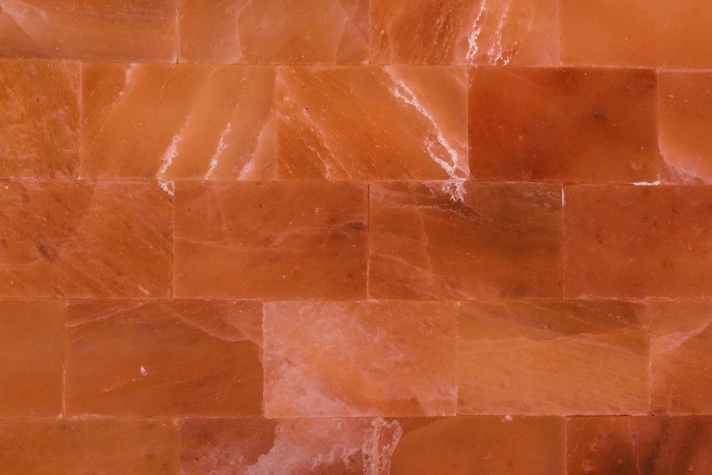 The Himalayan Salt Room is lined in rosy pink salt slabs.