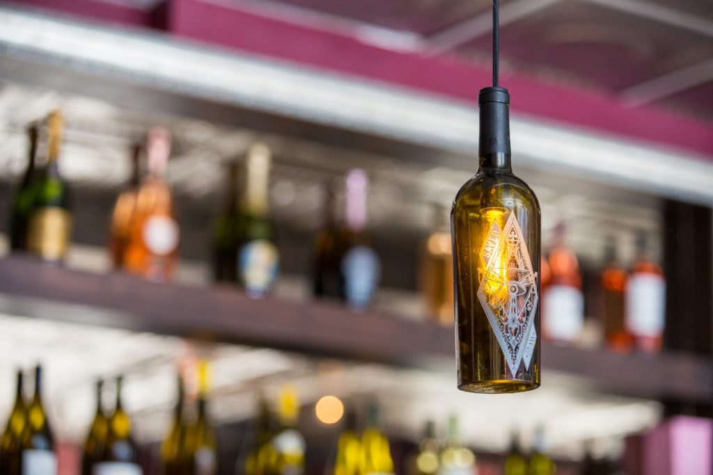 Yury Budovlya repurposed wine bottles to create lighting for Scopo Divino wine bar.