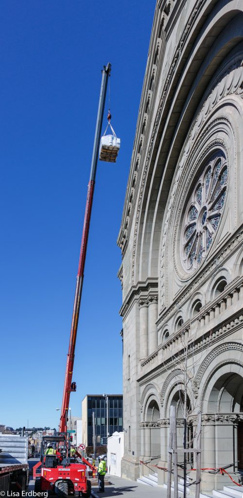 A crane hoists roofing material to the temple's historic dome.